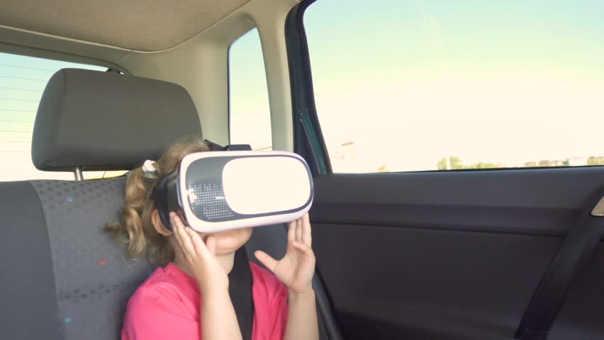 Little Girl a car rides around the city in the helmet of virtual reality. 360 VR Technology. | Shutterstock HD Video #30294466