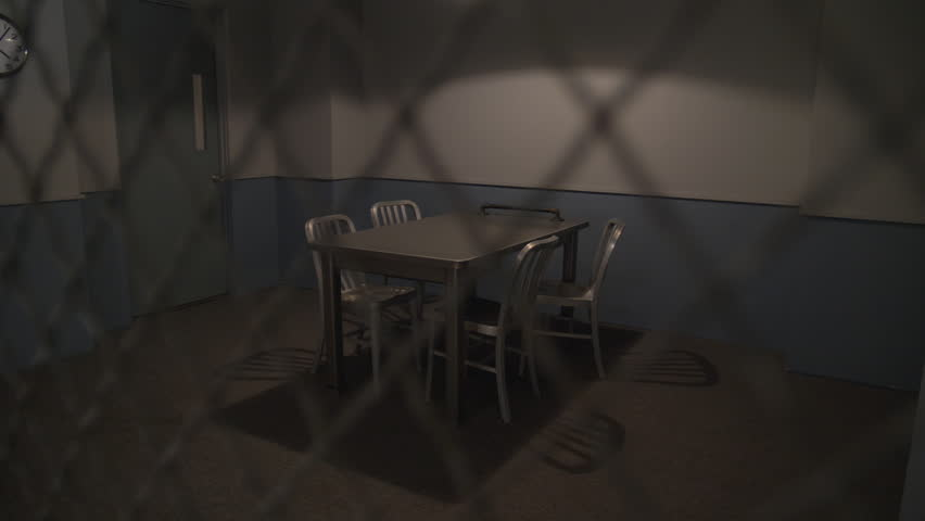 POLICE INTERROGATION ROOM.  Slow dolly move from behind a mesh barrier to an empty room.