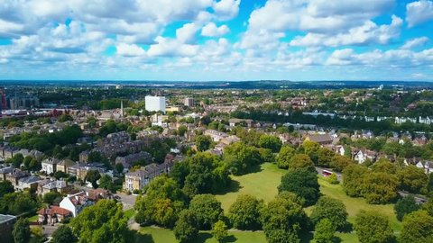 Aerial view of a leafy UK suburb on a summers day - camera rises