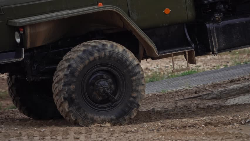 Slow motion close-up shot of spinning wheels of a military trucks