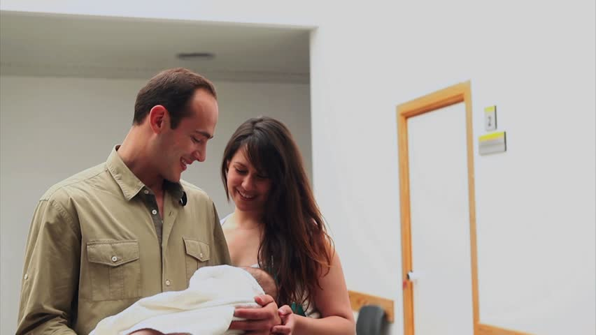 Smiling couple holding a new born baby in a hospital