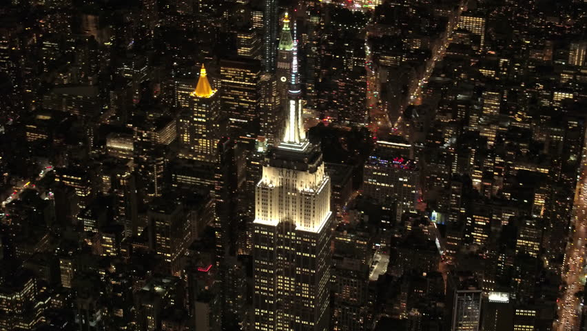 NEW YORK USA - SEPTEMBER 4, 2016,AERIAL HELI SHOT: Flying above the parallel streets under iconic Empire State Building shining lit up with lights on magical summer night in New York City.