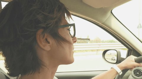 Woman with eyeglasses driving car with hands on steering wheel. Interior close up, side view, traffic on street. Vintage filter, toned image.