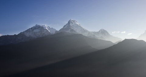 Sunrise in high mountains. Sunbeams move in morning mist under snowy peaks of Himalayan mountains, time-lapse
