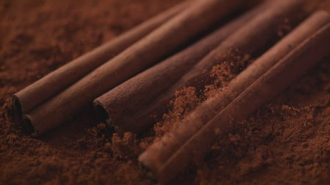 Cinnamon sticks falling into cinnamon powder. Shot with high speed camera, phantom flex 4K. Slow Motion.