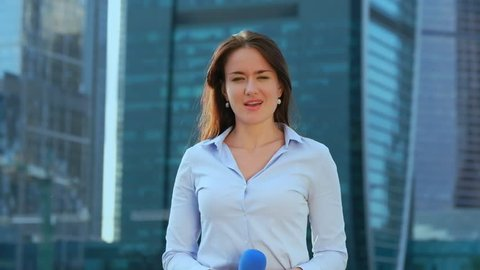 Young girl TV reporter is broadcasting on modern city background