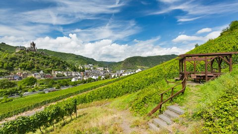 Summer vineyards timelapse at Moselle Valley with Cochem, Eifel in Germany in the background and the Reichsburg Cochem to the left. The wooden structure to the right is a lookout and resting place.