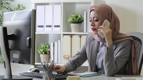 smiling attractive female muslim business woman using mobile cell phone talking with client discussing company case plan