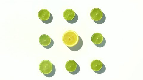 Lemons and limes chopped in half and spinning on a white surface