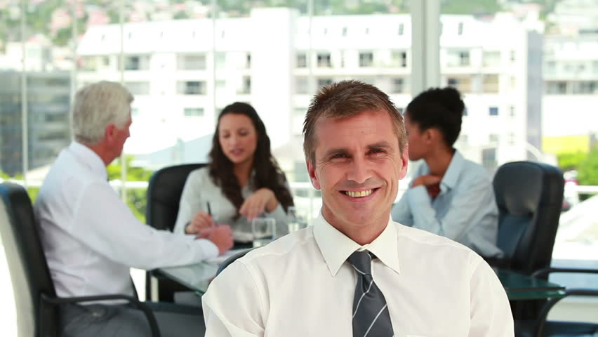 Portrait of a businessman with colleagues in meeting in background in a bright office | Shutterstock HD Video #3042013