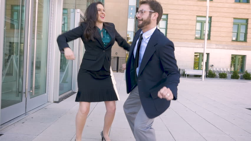 An attractive millennial man and woman business team celebration with a hive five and funky dancing outside a business complex in slow motion