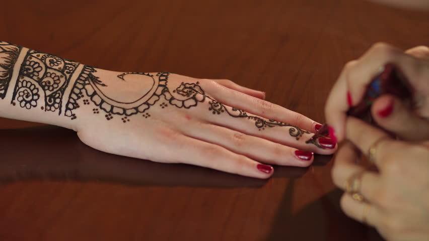 Mehndi For Tattoo : Woman making henna tattoo on hand close up mehndi is