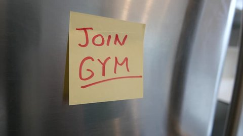 Putting a join Gym sticky note reminder on a fridge. Closeup on the hand and paper.