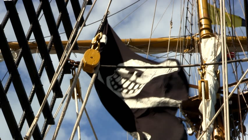 Pirate flag on tall ship Dewarcuci with blue sky and cloud background