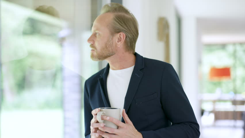 Portrait smiling man in modern home, drinking coffee next to window | Shutterstock HD Video #30465556