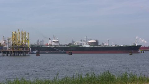 ROTTERDAM SEAPORT - JULY 2017: crude oil tanker Lyric Magnolia bunkering and unloads at Europoort (gate to Europe) industrial area with petrochemical refineries and storage tanks
