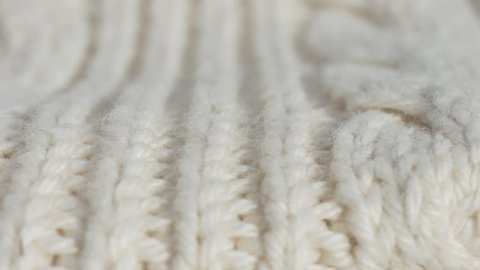 Amazing macro dolly shot of soft warm white woolen fabric to keep warm in winter. Christmas clothes.