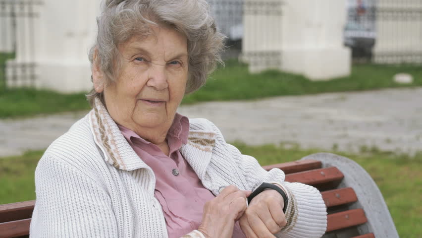 Black wristband. Mature elderly woman with gray hair aged 80s dressed in white jacket looks at the results of physical activity using a wristband fitness tracker outdoors in summer