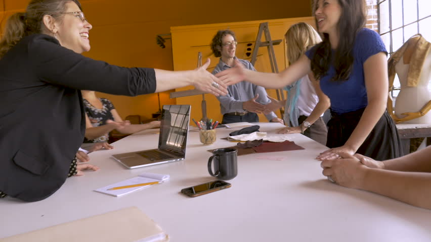 Empowered women and two men shaking hands at a brainstorming startup session celebrating business success in slow motion