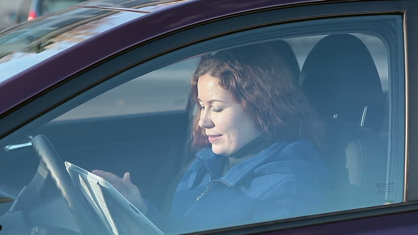 Woman using tablet pc behind closed car window glass