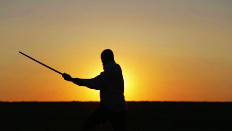 Portrait of a man with a sword at sunset, the path of a warrior. Samurai yakuza with a sword at sunset of the day. Sport, hobbies, interests.