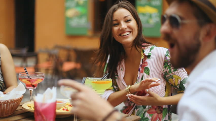 People, leisure and communication concept - happy friends meeting and drinking cocktails and eat nachos at street cafe, slow motion shot | Shutterstock HD Video #30559756