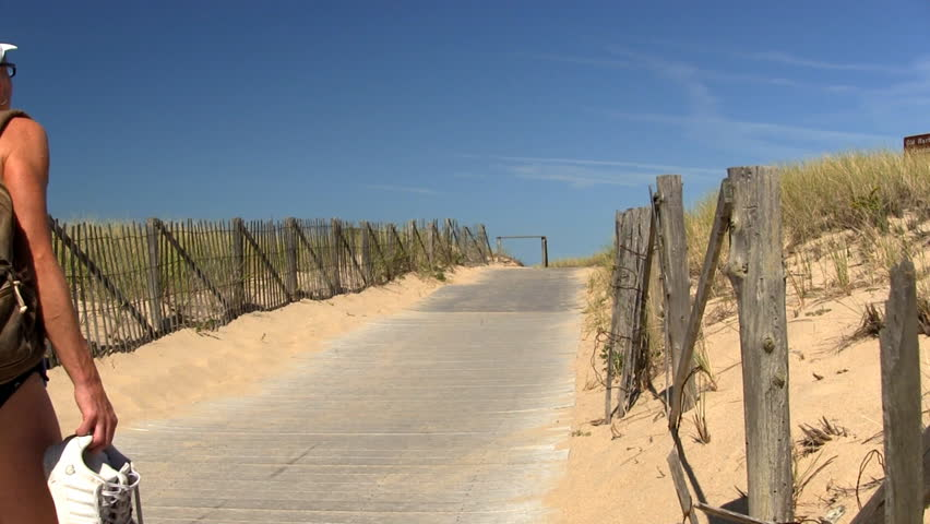 A woman walks across boardwalk through the sand dunes past wooden fence and tall beach grass of Provincetown on her way to race point beach to enjoy a beautiful summer day on Cape Cod