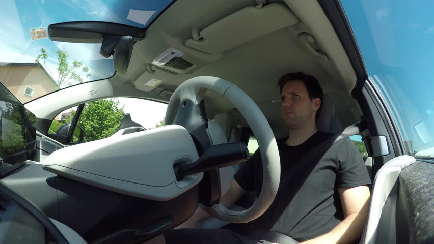 CLOSE UP, LOW ANGLE VIEW: Man driving in innovative autonomous automated electric car using self-parking autopilot for parallel parking on street. Robotic computer turning wheel in autosteering mode