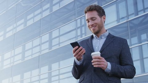 Business man drinking coffee using mobile cell phone app in city to play video games or text sms online. Young urban professional businessman enjoying coffee break relaxing using smartphone.