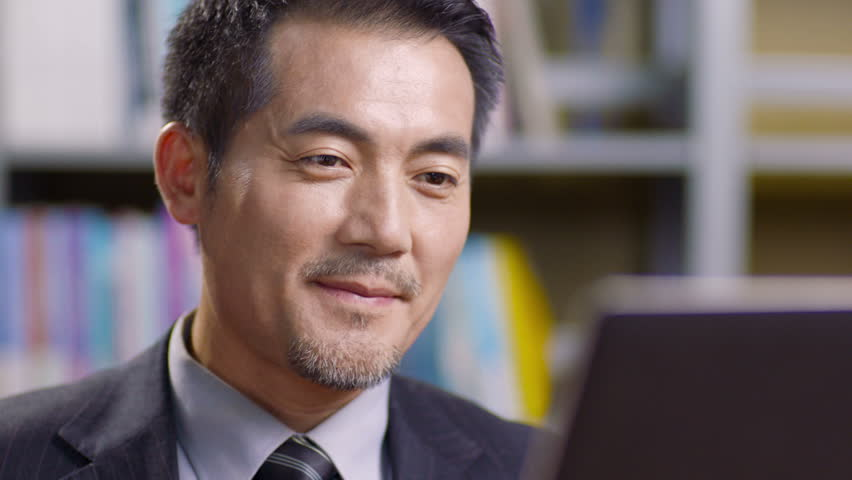 Closeup of asian corporate executive working in office using laptop computer. | Shutterstock HD Video #30612376
