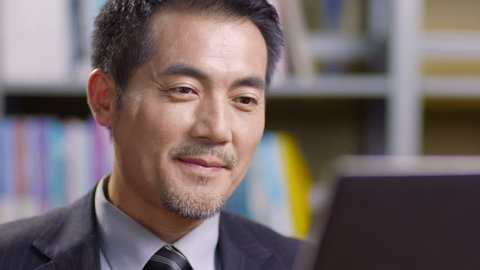 closeup of asian corporate executive working in office using laptop computer.