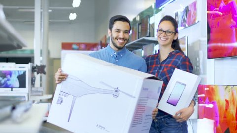 In the Electronic Store Happy Young Couple Poses with Newly Purchased Drone and Tablet Computer. Store is Big and Bright, Has All the Latest TV's, Cameras and Smartphones. Shot on RED EPIC-W 8K Camera