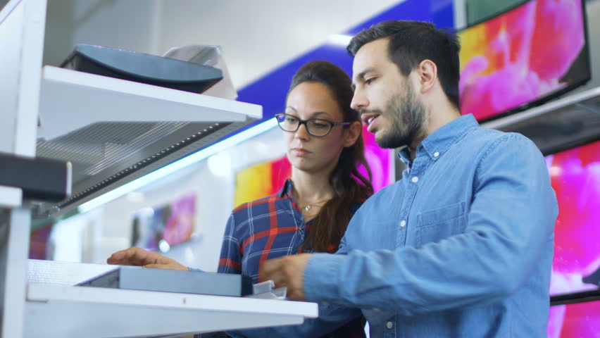 Beautiful Young Couple in the Electronics Store Browsing, Looking for Newest Gadgets, Tablets and Photo/ Video Cameras Presented on the Shelves. Shot on RED EPIC-W 8K Helium Cinema Camera. | Shutterstock HD Video #30614476