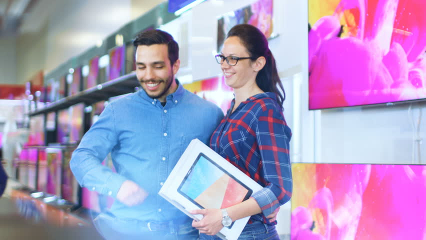 Young Couple Does Shopping In the Electronics Store, They've Already Chosen Latest Tablet Computer for Themselves. Store is Bright, Modern and Have all the Latest Electronic Devices. 4K UHD. | Shutterstock HD Video #30614506