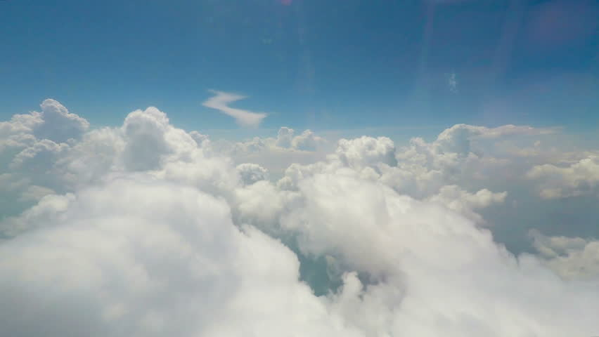 Big soft clouds floating in sky, interminable vast space, view from flying plane