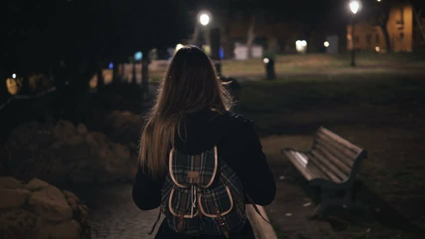 Back view of young stylish woman walking late at night through the dark park. going in the evening alone.