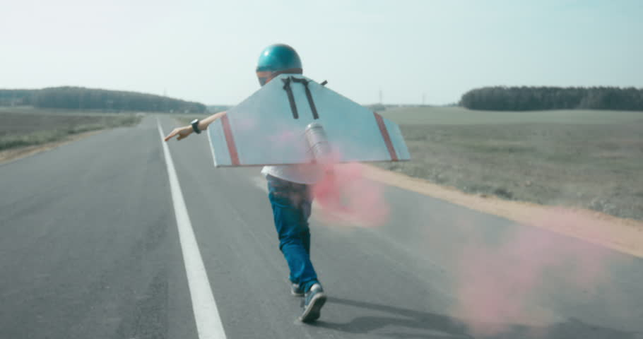 TRACKING Little boy wearing helmet and styrofoam wings running on a rural road, pretending to be a pilot. 4K UHD RAW edited footage | Shutterstock HD Video #30699526