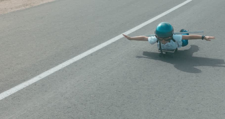 Little boy wearing helmet and styrofoam wings riding skateboard on a rural road, pretending to be a pilot. 4K UHD RAW edited footage