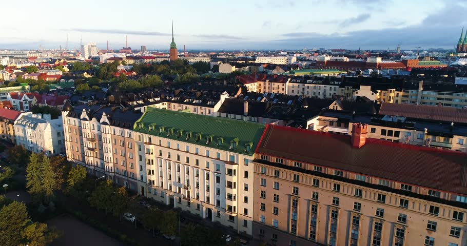 Aerial view of Helsinki capital of Finland. Drone rising during sunny summer clear  morning with some mist above city filming old buildings and lots of colorful rooftops. Eira. Ullanlinna.