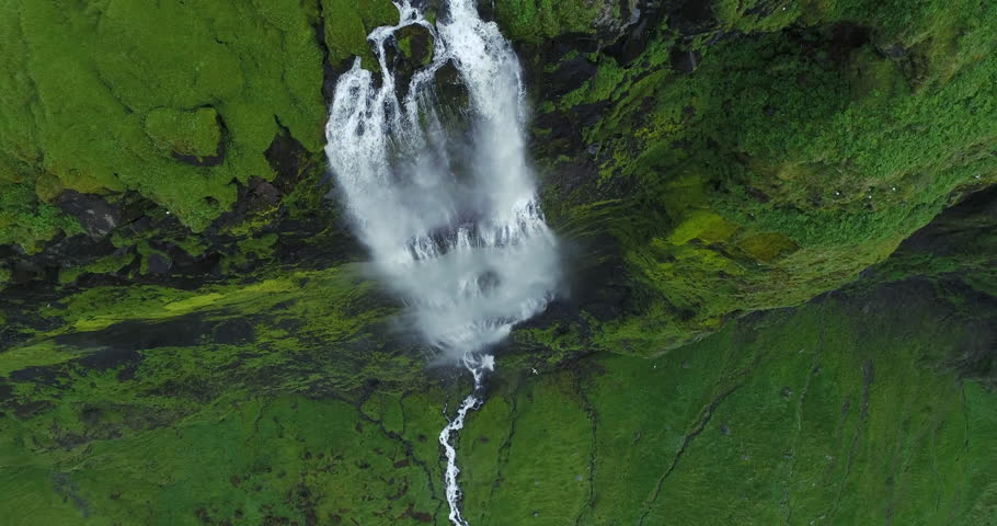 Slow motion aerial of huge waterfall and cliff