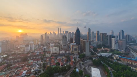 Time lapse: Beautiful and dramatic sunrise view of the Kuala Lumpur skyline overlooking the city, Tilt Up