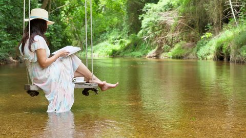 Advertising,Time to relax, Lifestyle, Fashion, Travel concept - Asian woman sitting on wood swing hanged on a tree, swaying gently and reading book. A river flows in beautiful scene. (Water stream)