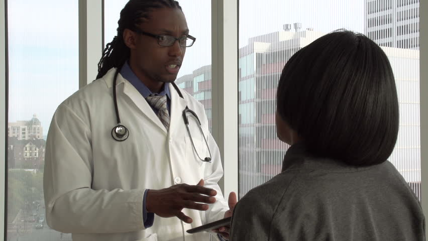 Doctor discussing results with patient on tablet