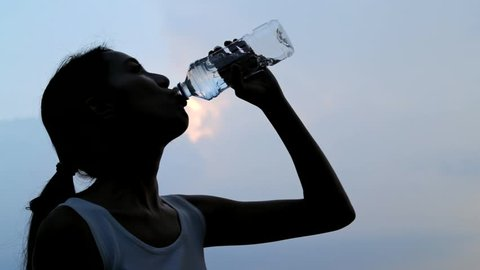 Slow motion of woman drinking water in sunset time