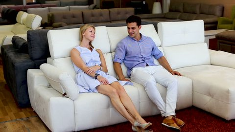 Happy couple are choosing new sofa in furniture store