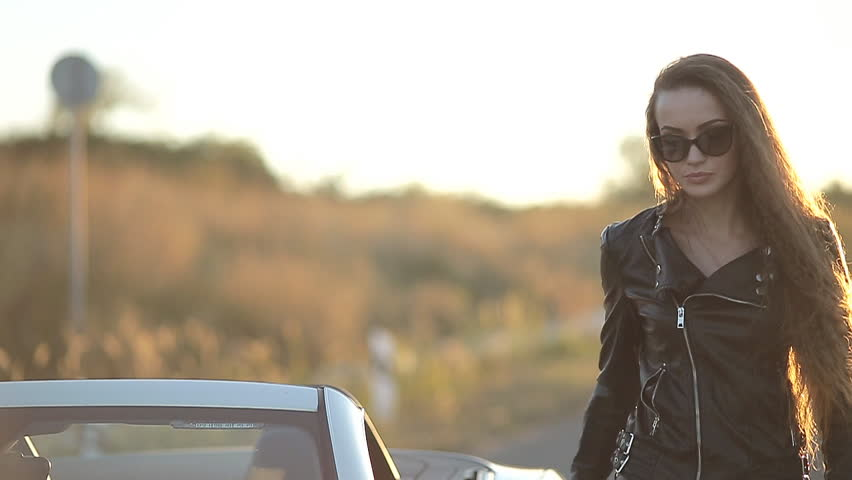 ba84c0b7e beautiful sexy girl with long hair in a leather jacket and leather pants in  sunglasses gets out of the car at sunset