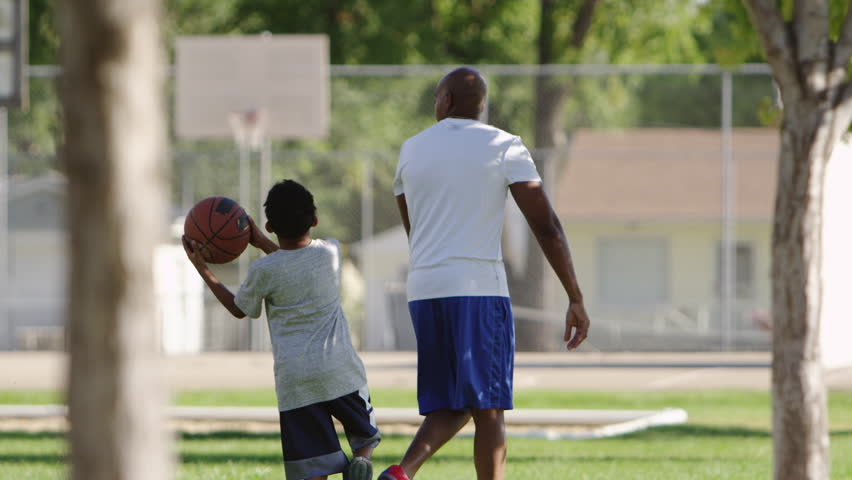 Father and son enjoy a day at the park, playing basketball. | Shutterstock HD Video #30790816