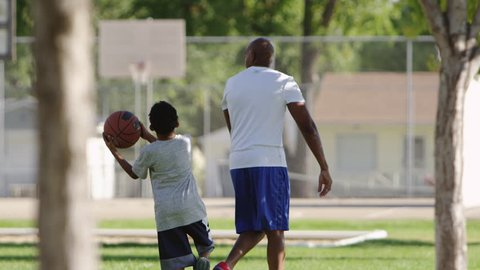 Father and son enjoy a day at the park, playing basketball.