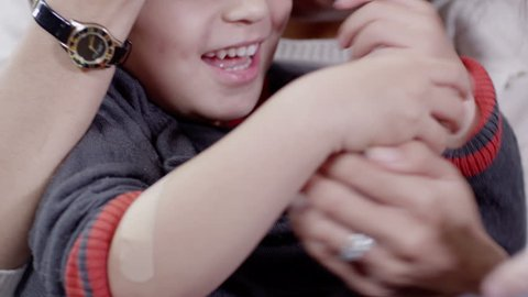 Little boy gets a sticking plaster on his arm