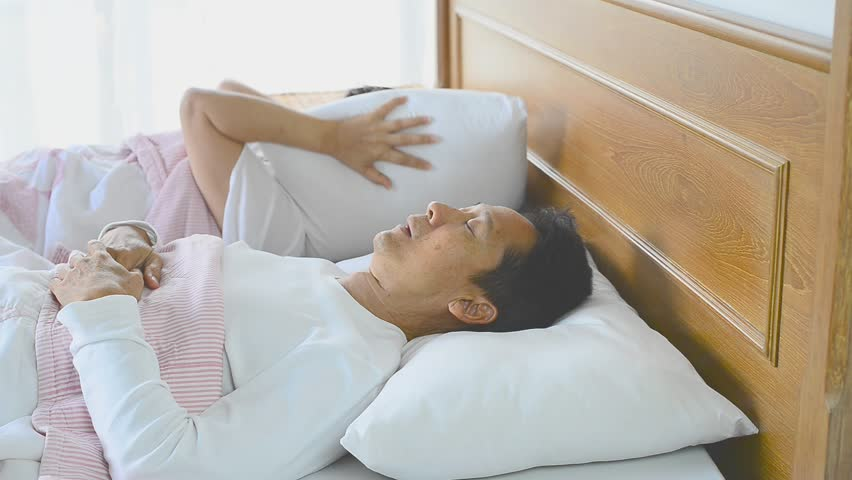 Snoring man choking out loud waking his wife up during the noisy night and she close ears with pillow. Obstructive sleep apnea symptoms .